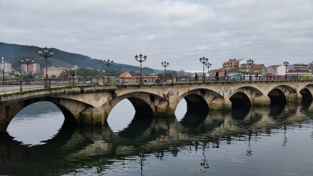 Паломники идут в Сантьяго по римскому мосту